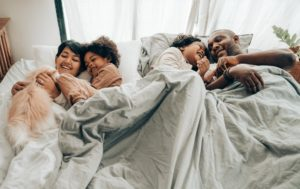 A family laying in bed together smiling and laughing