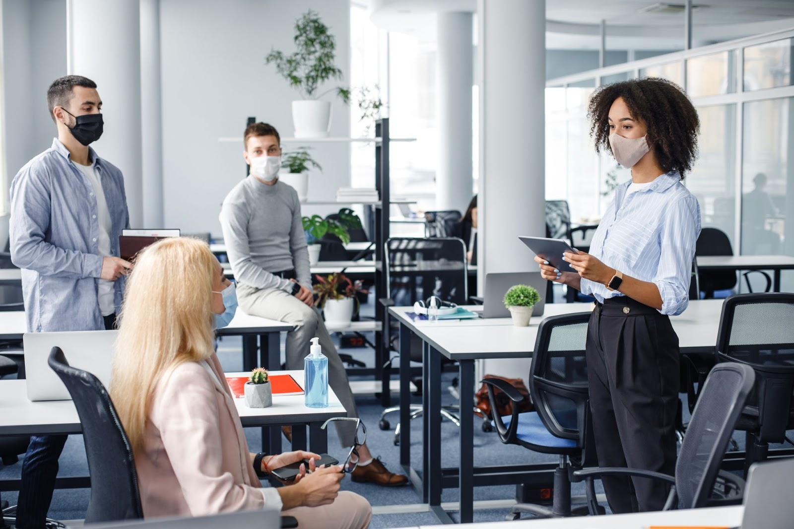 Group of male and female coworkers holding a meeting in an open workspace